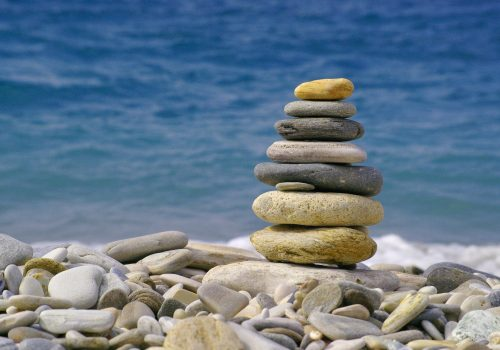 pile of stones amidst other stones on beach intended to show the 80/20 rule
