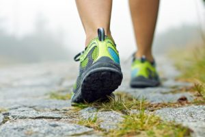 running shoe clad feet of woman walking along a grass and stone path