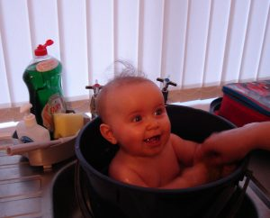 baby taking a bath in a bucket set in the kitchen sink