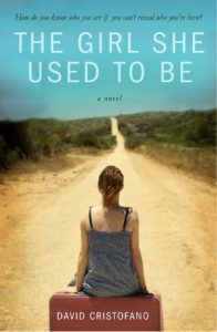 book cover of The Girl She Used to Be girl sitting on suitcase staring at dusty road extending into the distance