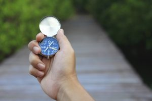 hand holding compass with wooden path beyond, symbolic of planning my immunity to change map