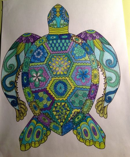 sea turtle colouring page completed in various shades of green, blue and purple