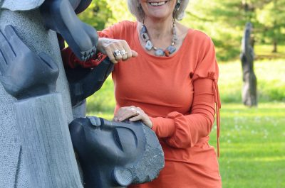 Portrait of Fran Fearnley curator of ZimArt with one of the sculptures