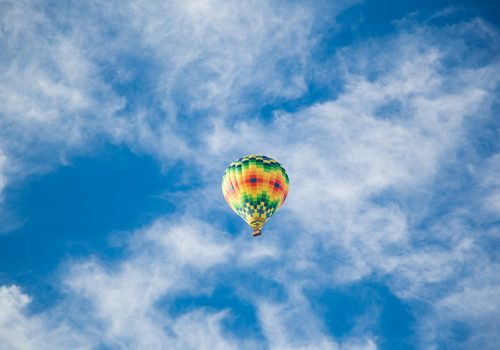 hot air balloon in a blue sky with wispy clouds