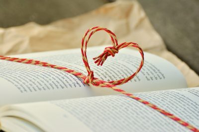 open book with red cord tied into a heart shape for read a book in one sitting