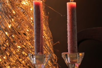 two red taper candles with a textured gold cone in the background