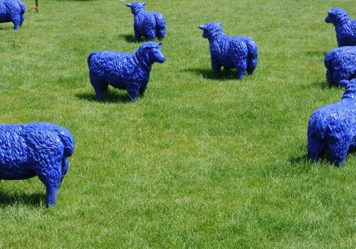 bad art blue plastic sheep in a field