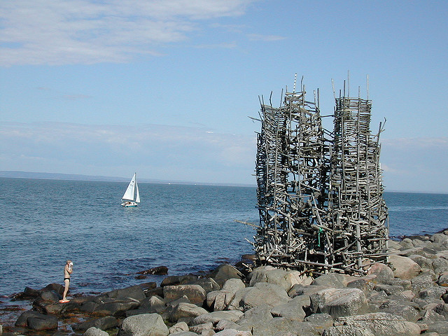 Nimis sculpture of driftwood in front of sea with boat