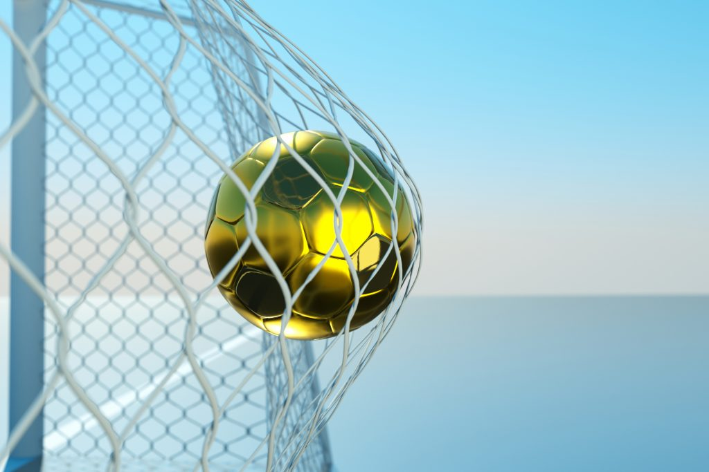 gold coloured soccer ball in net at goal, blue water and sky background