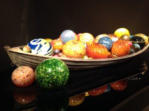 wooden boat containing many different coloured glass balls by Dale Chihuly