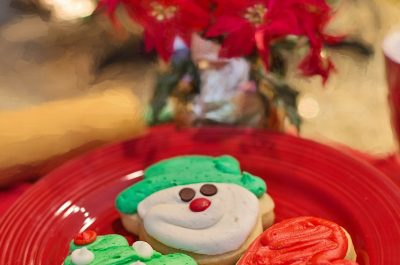 decorated sugar cookies on red plate with poinsettia in background