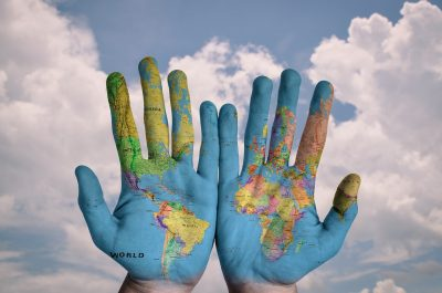 map of world painted on hands held up in front of sky micronation possibilities