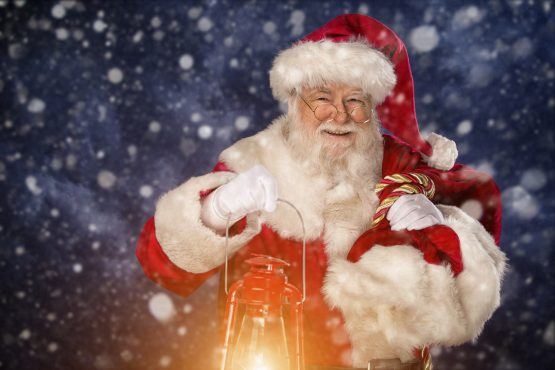 Professional Santa carrying lit lantern and sack against blue starry sky