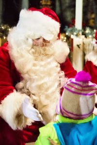 santa claus extending hand to child. child's face is not seen