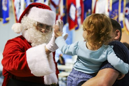 Santa Claus highfiving a young child in her father's arms