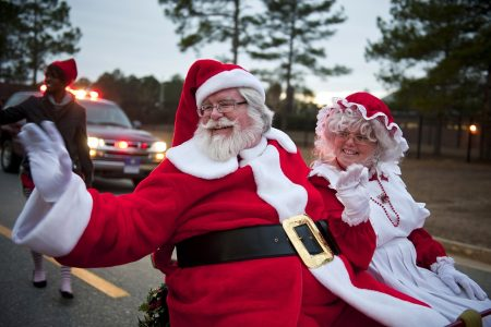 Professional Santa Claus and Mrs. Claus waving from a parade float