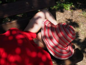 young woman having a power nap one hand behind her head, summer hat covering her face, on a bench in dappled sunlight