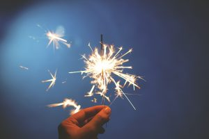 woman's hand holding a sparkler making new year's resolutions against a blue sky