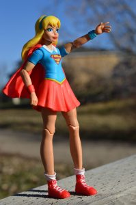 plastic toy supergirl posed against field