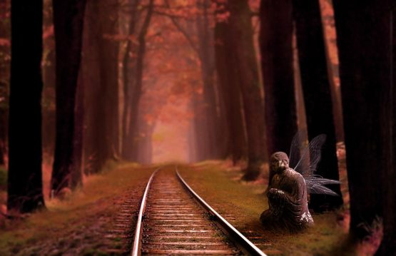 a railroad track disappearing into the distance, leafed trees on either side, a buddha sculpture with fairy wings perched by the track