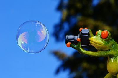 ceramic frog taking photo of soap bubble