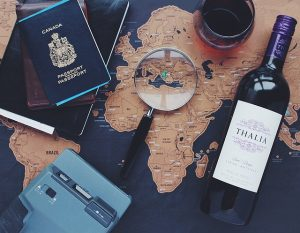 Canadian passport, map, magnifying glass, red wine and taperecorder