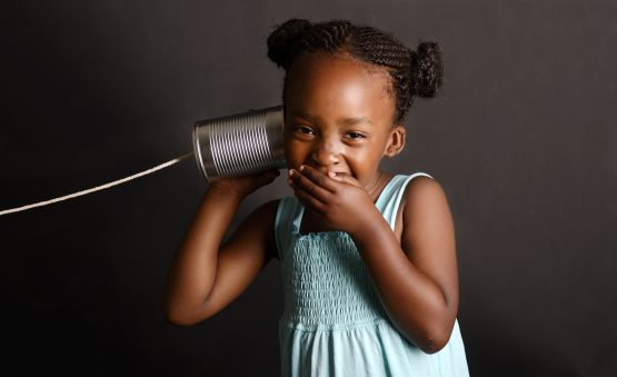 young black girl listening to tin can telephone
