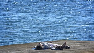 person meditating laying down at edge of water