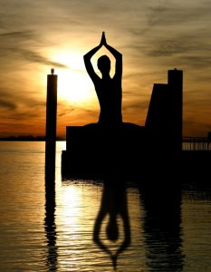 silhouette and reflection of woman meditating