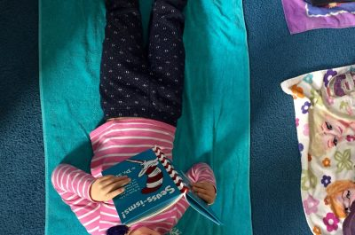 Young girl lying on mat reading a Dr. Seuss book