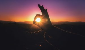 hand making okay symbol in front of sunset