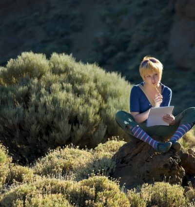 Girl sitting on the rock and thinking with notebook