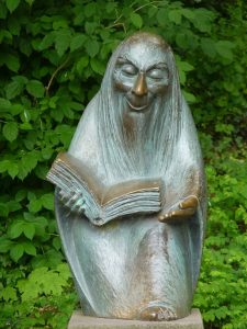 stone sculpture of ancient bearded storyteller with book in hand