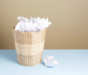 wicker garbage can filled with crumpled white paper
