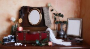 vintage scene - open suitcase, two empty frames, roses in vase, tie, camera, scarf