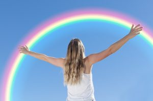 back of long haired woman, hands extended to a rainbow