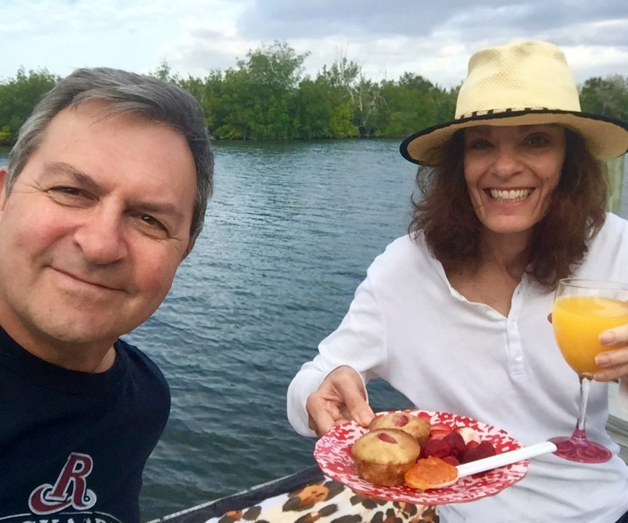 Donna Connolly and husband holding plate of muffin and fruit plus orange juice