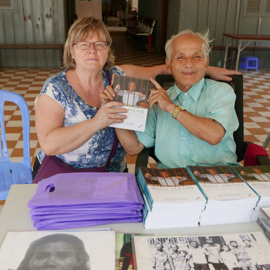 Survivor in Cambodia showing his book