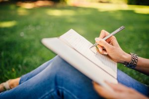 woman writing in notebook showing only legs hands, pen and notebook