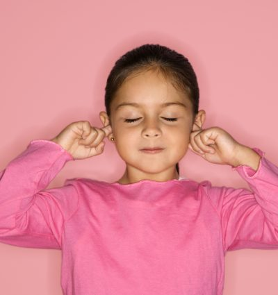 Young girl with eyes closed and fingers in ears