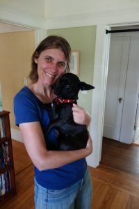 woman hugging small black dog