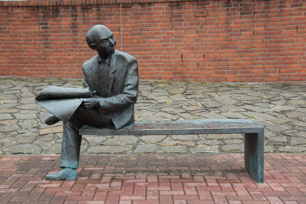 sculpture of man on bench reading newspaper