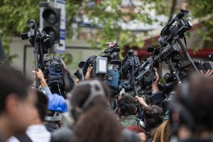 cluster of press people gathering with cameras