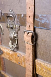 closeup of antique trunk showing strap and lock