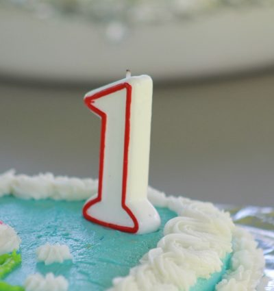 birthday cake with blue and white icing and the number 1