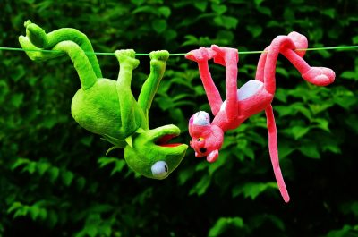 Kermit and pink panther dolls hanging upside down on a wire