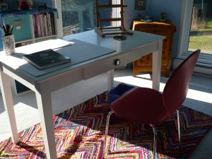 table and colourful rug in art studio