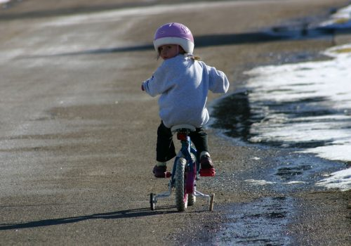 young girl on bike with training wheels