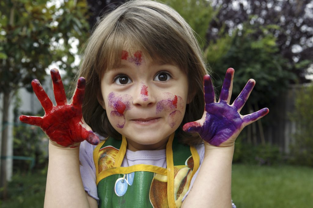 happy young girl hands covered in paint
