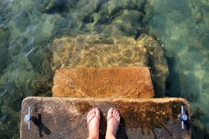 woman's feet on top step descending into the sea